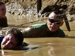 Contestants slither through mud to get beneath barbed wire. Photo by Alhele Curry.